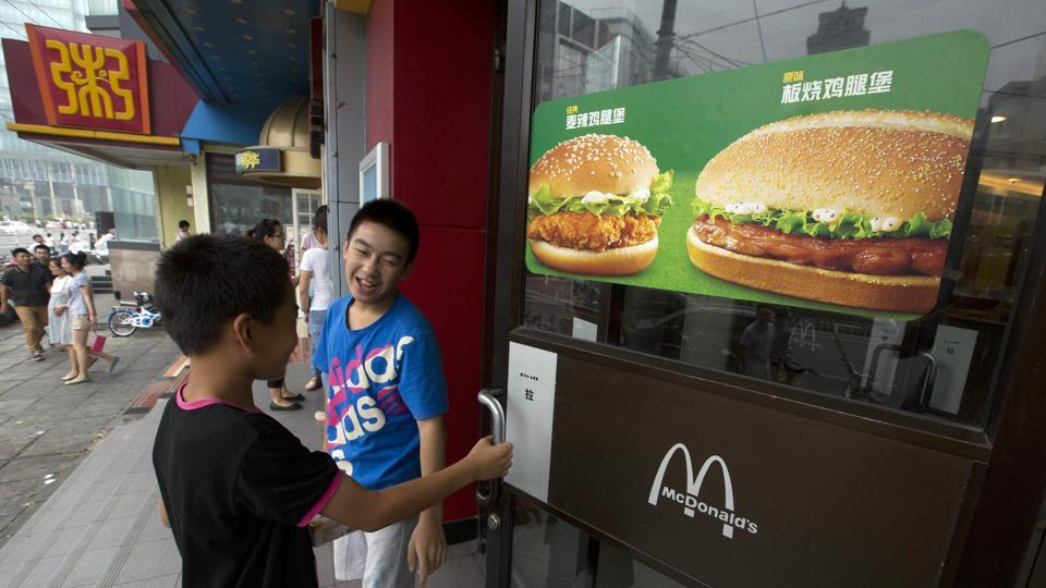 File photo of two boys opening the door to a McDonald's restaurant in Beijing, China. On August 8, 2017, McDonald's said it plans to nearly double the number of restaurants in China in the next five years, eventually surpassing Japan as the chain's second-biggest market outside the United States.