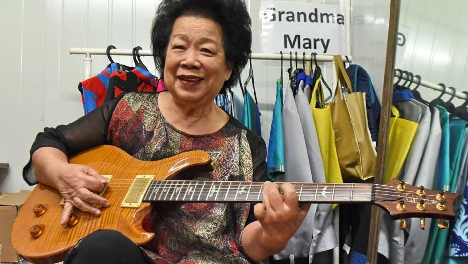 Mary Ho, also known as Grandma Mary, posing with her electric guitar during a rehearsal in Singapore on August 5, 2017.