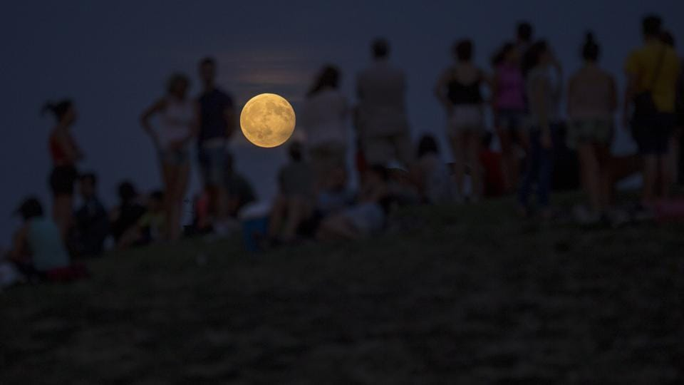 People watch a rising full moon during a partial lunar eclipse atop a hill at the Tio Pio park in Madrid. A lunar eclipse or solar eclipse is not visible every month as the moon's orbit is tilted about 5 degrees off from Earth's orbit.  (Francisco Seco/AP)