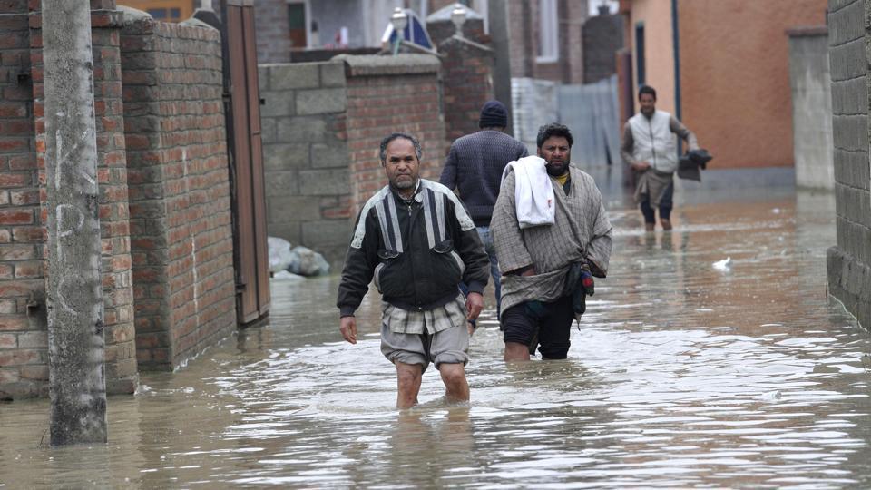 A Kashmiri men wades through a flooded road in Srinagar.