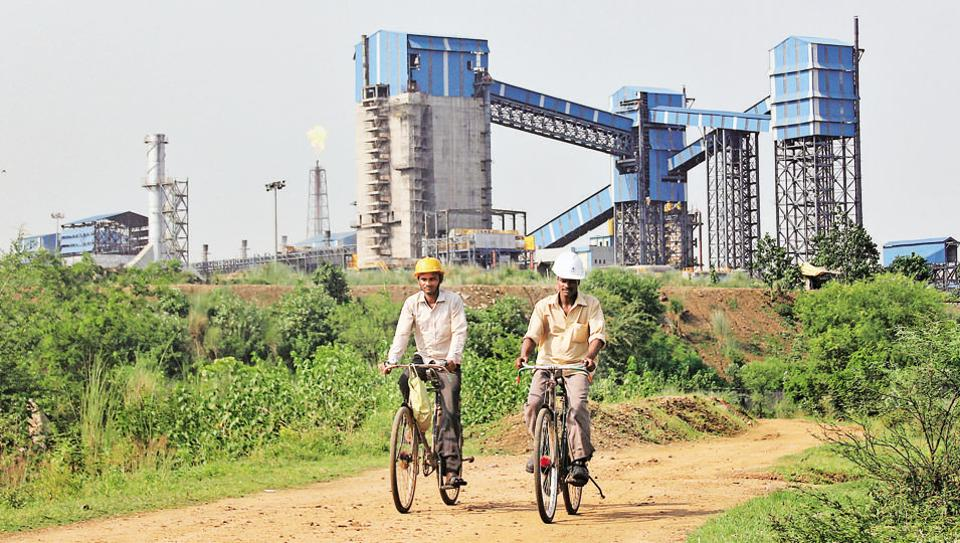 """Men ride their bicycles in front of the Bhushan Steel plant in Odisha. Bhushan Steel is part of India's """"NPA crisis"""" that have choked the banking system and pushed lending, the lifeblood of the economy, to its lowest point in 20 years."""