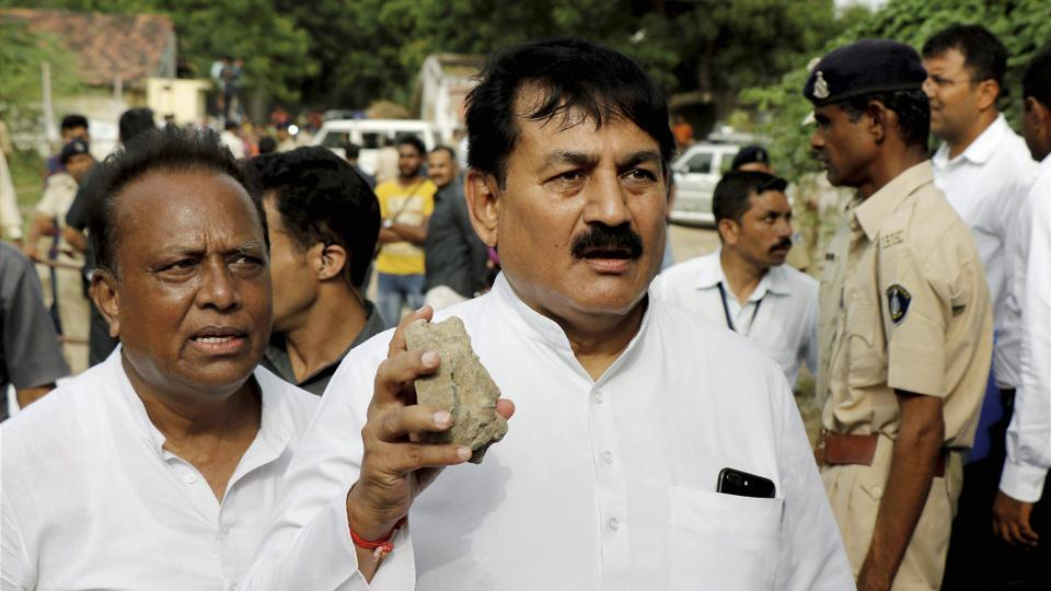 Senior Congress leader Bharatsinh Solanki hold a stone that was allegedly thrown at party vice president's Rahul Gandhi's car during his visit to flood-hit Dhanera village in Gujarat's Banaskantha district last week.