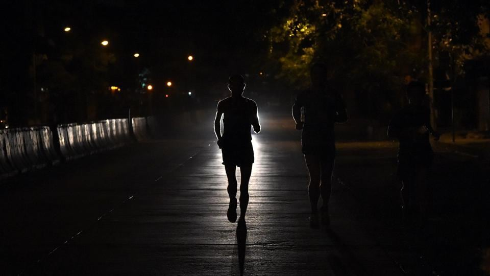 Samir Singh (C) is silhouetted by car's headlights during an early morning sprint in Mumbai. Dressed in a blue sports vest, Singh started each day in the early hours from the northern Mumbai slums and headed to the business district in the city's south. (Indranil Mukherjee / AFP)