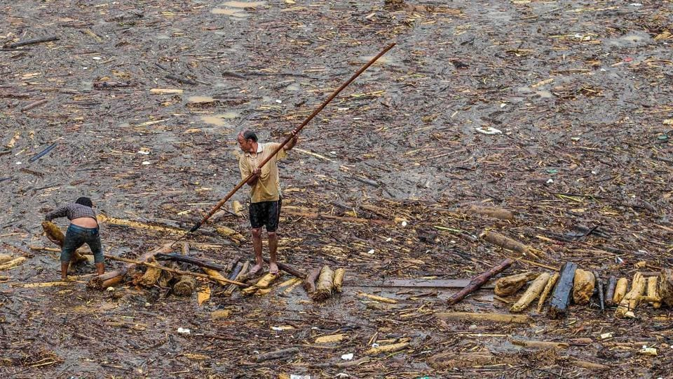 Two men collect wood from a lake filled with timber brought down from the mountains by flash floods, in the mountainous district of Mu Cang Chai in Yen Bai, Vietnam. Floods and landslides in northern Vietnam have killed at least 26 people and washed away hundreds of homes over the past week. Fifteen people are still missing. (AFP)
