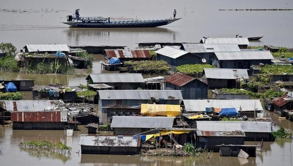 Villagers in a boat row past partially submerged houses in a flood-affected village in Morigaon district of Assam. (REUTERS)