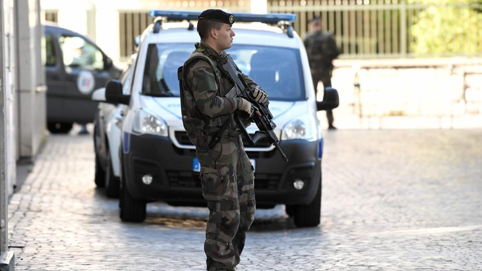 An armed French soldier stands near the site where a car slammed into soldiers on patrol in Levallois-Perret, outside Paris, on August 9, 2017.