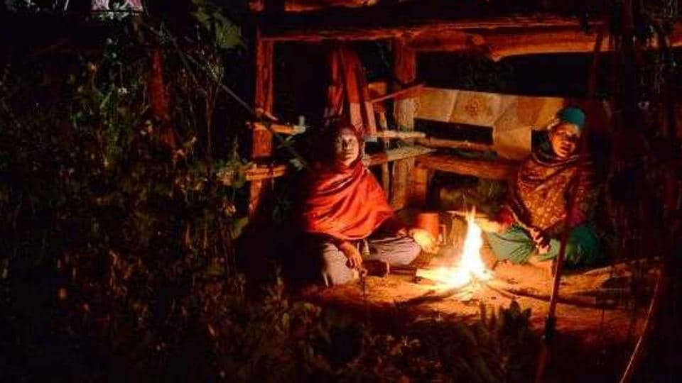 Nepalese women Pabitra Giri and Yum Kumari Giri sit by a fire as they live in a Chhaupadi hut during their menstruation period in Surkhet District.
