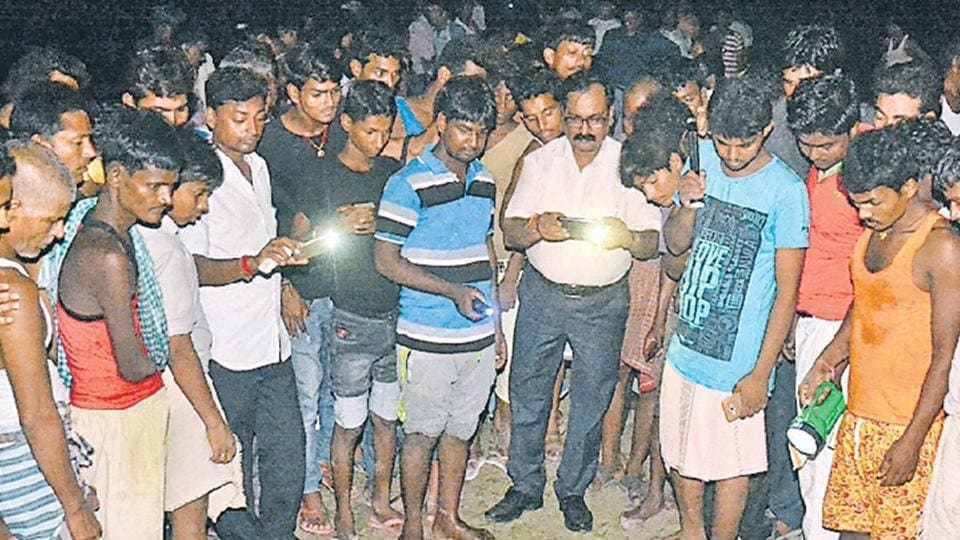 A crowd near the seasonal shallow lake where bodies of four children were recovered in Muzaffarpur district.