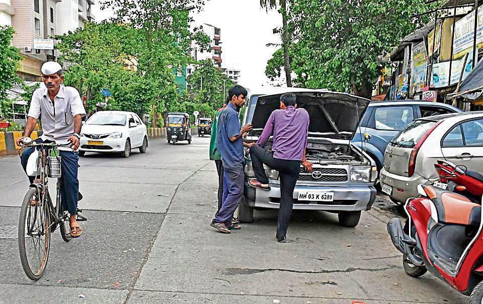 Mechanics repair a car at Juhu-Versova Link Road.