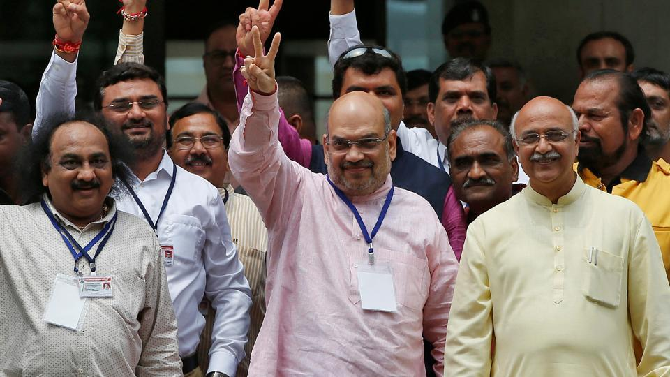 Amit Shah, President of BJP, along with his party's lawmakers gestures after casting his vote for three crucial seats in the Rajya Sabha, outside a polling centre in Gandhinagar, India, August 8, 2017.