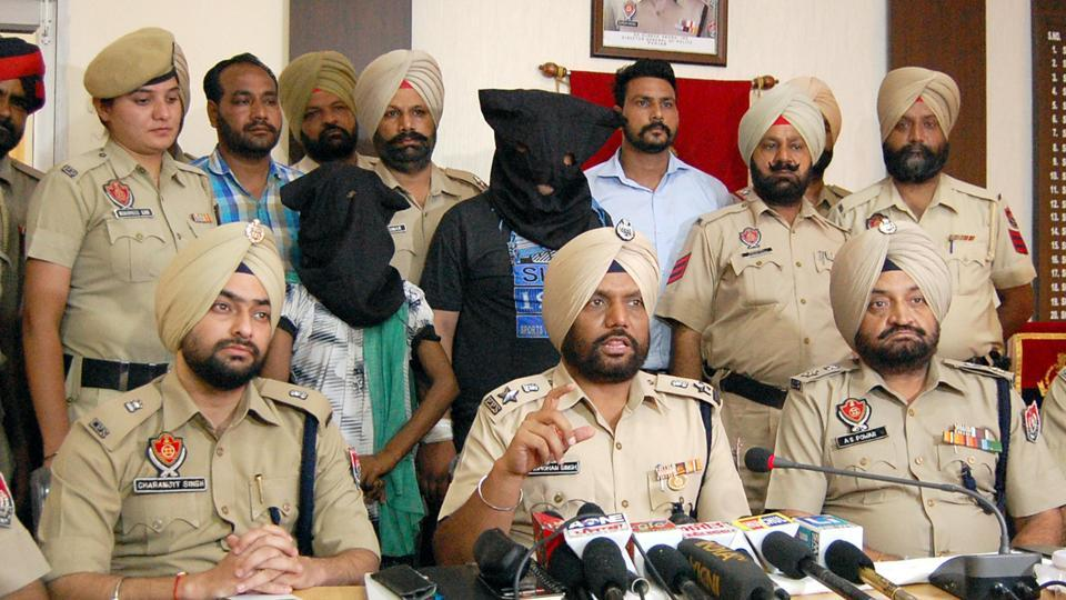 DCP (investigation) Jagmohan Singh and other cops with the two persons arrested, in Amritsar on Wednesday, August 9.