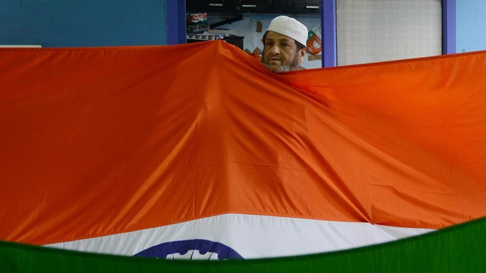 A man folds the tricolour for sale ahead of the upcoming Independence day celebrations at a workshop in New Delhi. (Money Sharma/AFP)