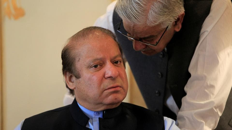 Former Pakistan prime minister Nawaz Sharif speaks with foreign minister Khawaj Asif during a meeting in Islamabad on August 9, 2017.