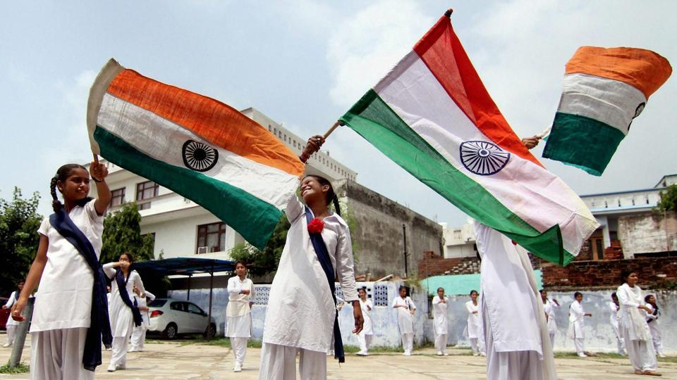 School children wave the national flag during a rehearsal for celebrations to be held on the occasion of 70th Independence Day at a government school, in Jammu. (PTI)
