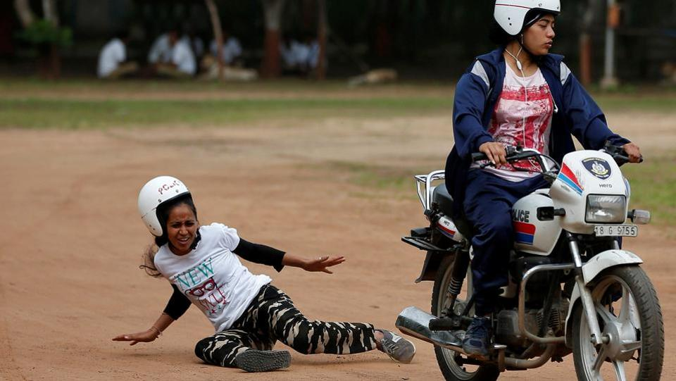 A policewoman reacts after a fall from a motorcycle while taking part in a rehearsal for Independence Day celebrations in Ahmedabad, Gujarat.  (Amit Dave/REUTERS)