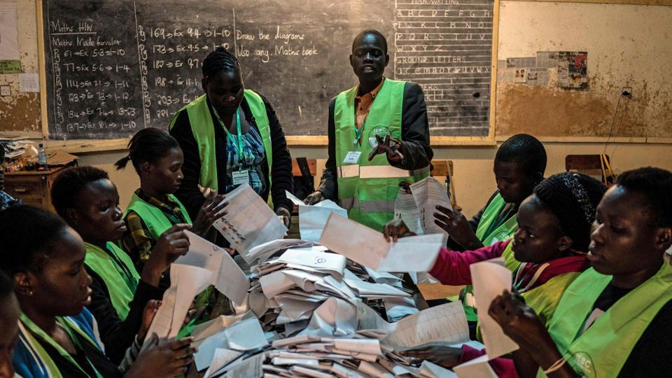 Voting officials count ballots at the Victoria primary school polling station in Kisumu. After the voting, officials ensured  that the  ballots were properly counted, which was being done manually and matched with electronic data in an effort to ensure no ballot stuffing occurred. (Fredrik Lernery/AFP)