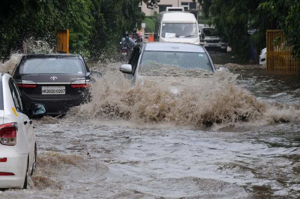 Cars ply through a water logged road after heavy rain in sector-31.