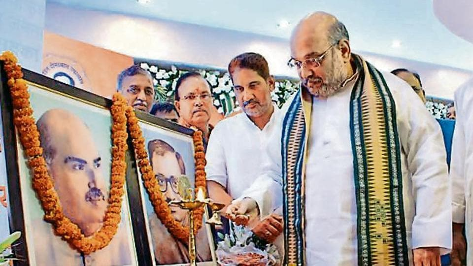 BJP national president Amit Shah pays tributes to Dr Syama Prasad Mookerjee (L) and Deendayal Upadhyaya in Rohtak.