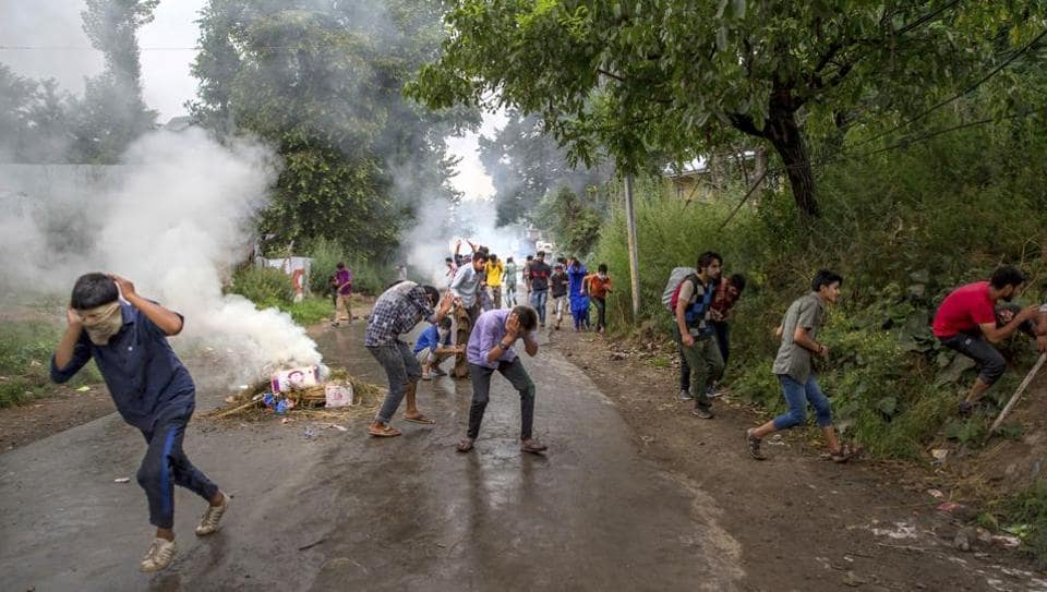 Kashmiri villagers run for cover as policemen fire pellets during a protest after the funeral procession of  a teenage boy in Haal village in Kashmir.