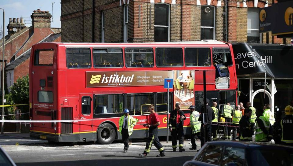 Emergency workers and officials examine the scene of an accident where a London bus ploughed into a shop on a busy street in southwest London on August 10, 2017.
