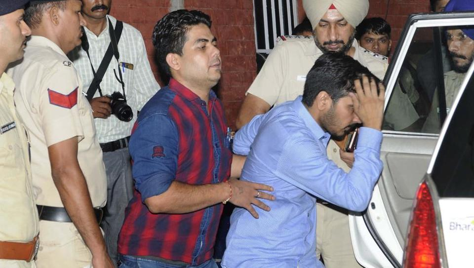 Vikas Barala (in blue shirt) being taken into police custody on Wednesday.