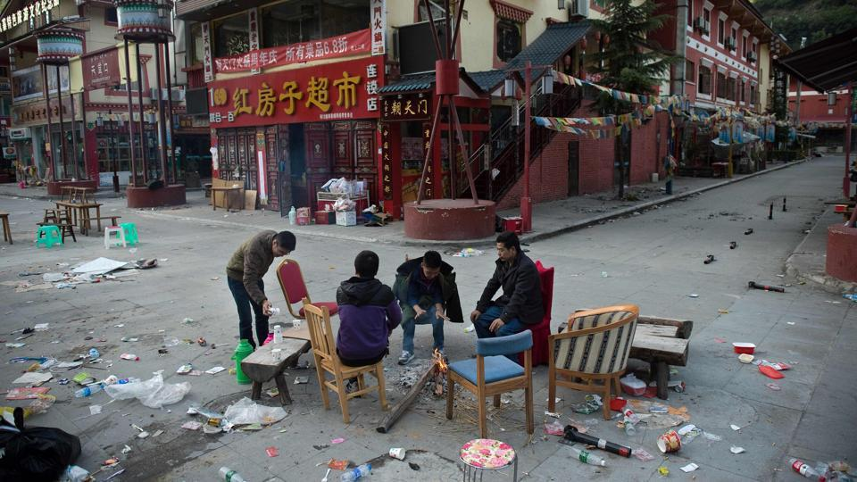 Residents, who slept outside their homes for fear of aftershocks after an earthquake, sit around a fire to warm up in Zhangzha in southwest China's Sichuan province on August 10, 2017.