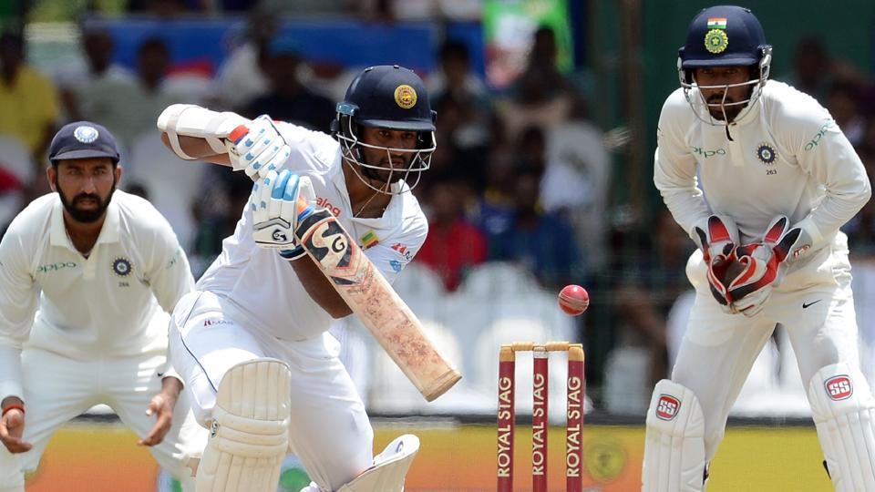 Dimuth Karunaratne (C) is watched by Wriddhiman Saha (R) as he plays a shot during the fourth day of the second Test match between Sri Lanka and India.