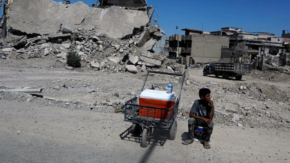 An Iraqi boy sells water in front of destroyed houses on a street in Western Mosul, Iraq August 7, 2017.