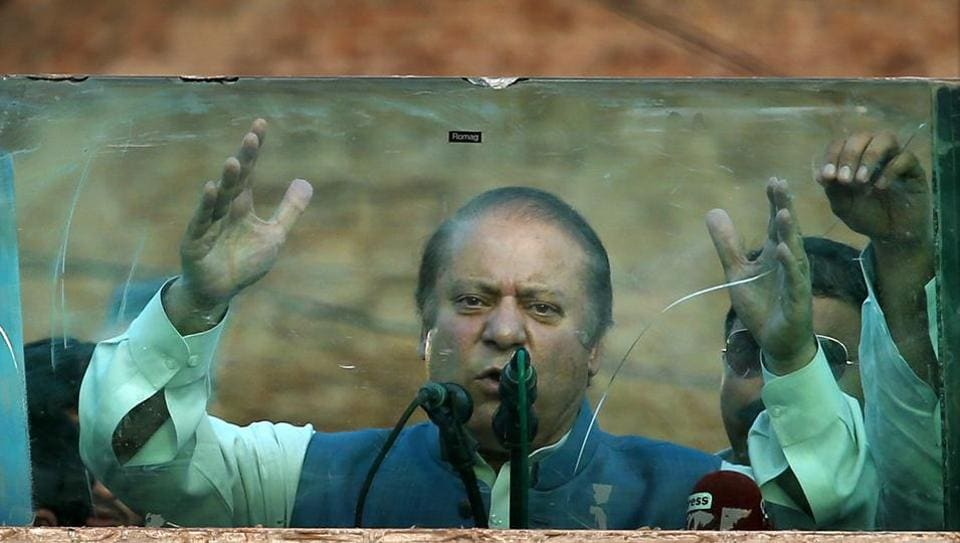 Deposed Pakistani Prime Minister Nawaz Sharif addresses his supporters behind glass during a rally in Jhelum, Pakistan, on August 10, 2017.
