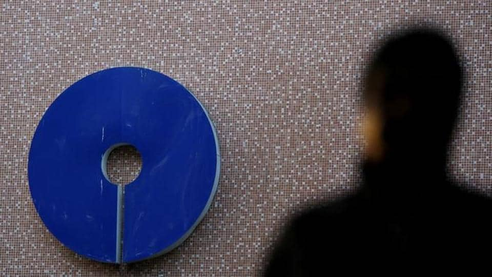 A man walks past a logo of State Bank of India outside a branch in New Delhi.