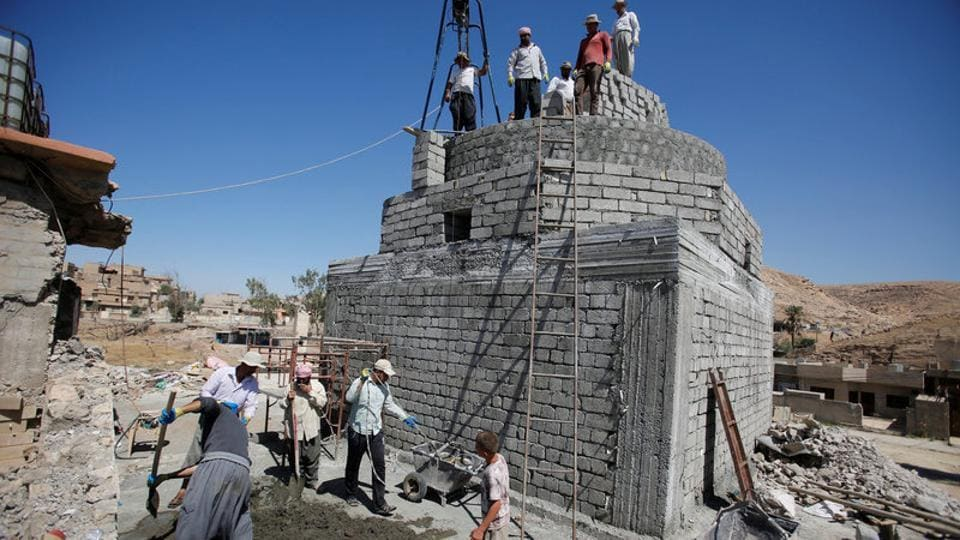 Workers rebuild a Yazidi shrine, after is was destroyed by Islamic State, in Bashiqa, a town near Mosul, Iraq August 8, 2017.