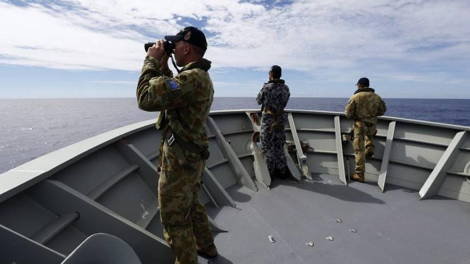 Crew members on the Australian Navy's HMAS Perth scan the Indian Ocean for debris from Malaysia Airlines Flight MH370.
