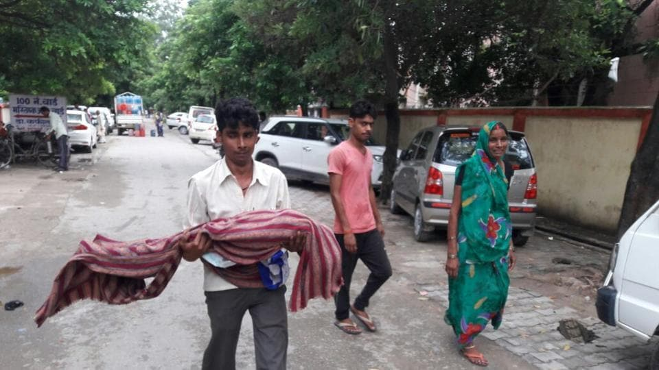 A relative carrying the body of a child who died at the Baba Raghav Das Medical College in Gorakhpur.