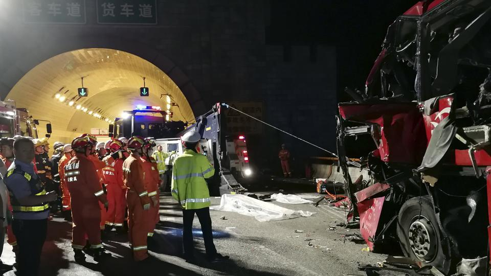 In this photo released by China's Xinhua News Agency, first responders work at the site of an accident after a coach hit the wall of the Qinling Mountains No. 1 Tunnel on the Jingkun Expressway in Ningshan County, northwestern China's Shaanxi Province, Friday, Aug. 11, 2017.