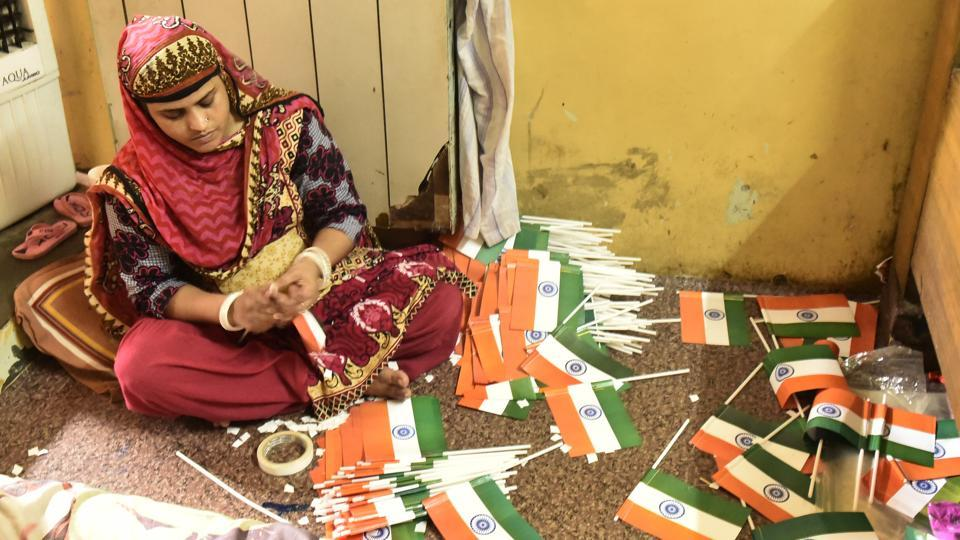 Demand for the tricolor comes in all sizes. From large cloth banners that take place on masts high up the skyline to small  hand held versions that are sold by at every corner by hawkers. A woman prepares versions of the latter at her residence which also doubles as a workshop. (Burhaan Kinu / HT Photo)