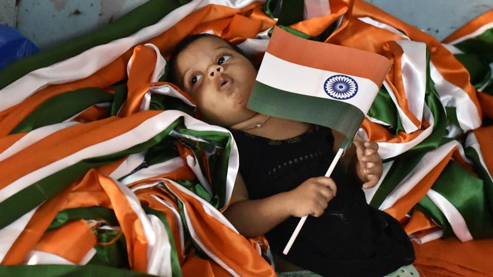 A little girl holds on to a national flag, laying in a heap of tricoloured ribbon as other family members are busy completing orders at a flag making workshop in Old Delhi. (Burhaan Kinu / HT Photo)
