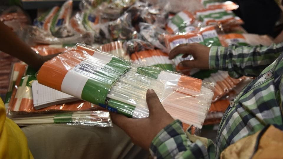 A person buys Indian national flags in bulk at a market for the upcoming Independence day celebrations, in New Delhi. Tricolour related paraphernalia ranging from flags to face paint, clothing and banners sees exceptionally high demand among buyers in the days leading up to the eve of August 15. (Burhaan Kinu / HT Photo)