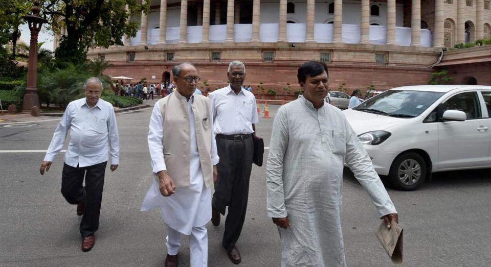 Congress leader Digvijay Singh and CPI member D Raja with JDU leader Ali Anwar Ansari leave after attending the monsoon session at Parliament in New Delhi.