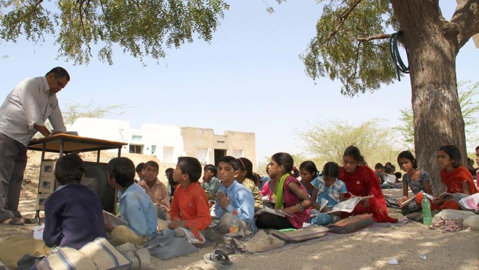 Students attend class under a tree at a government school in Rajasthan.