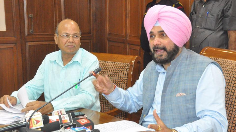 Minister Navjot Singh Sidhu, accompanied by former customs officer SL Goyal, speaking at a press conference in Chandigarh on Saturday.