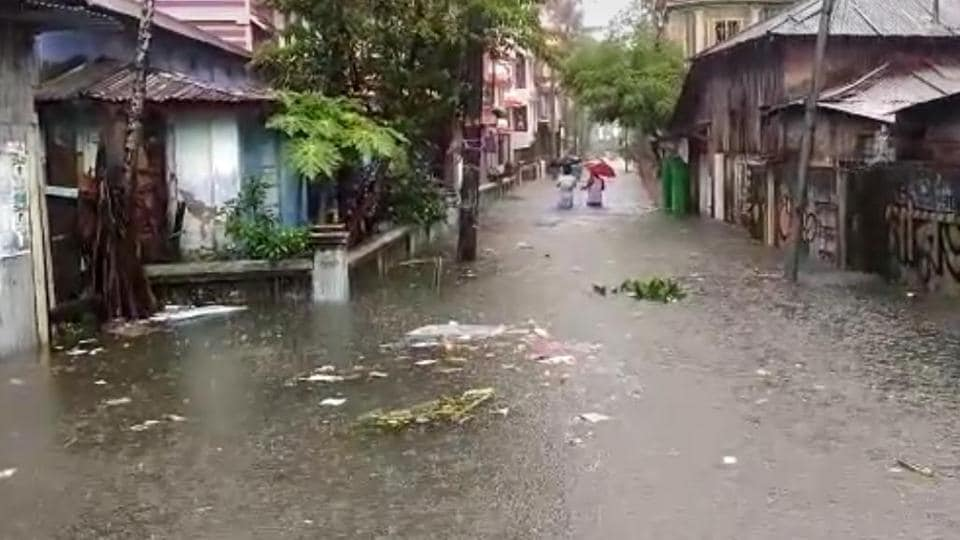 People wade through waist-deep water in Cooch Behar as heavy rainfall and overflowing rivers flood large parts of north Bengal.