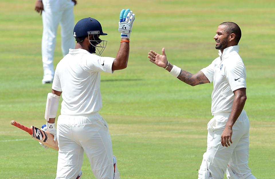 Indian cricketer Shikhar Dhawan (R) is congratulated by his teammate Cheteshwar Pujara after he scored his century. (AFP)