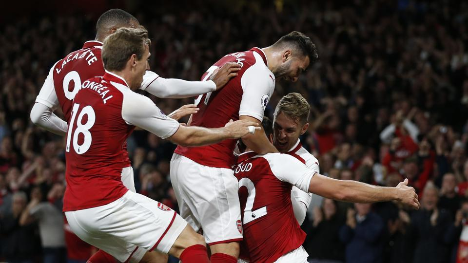 Arsenal's French striker Olivier Giroud (2nd R) celebrates with teammates after scoring Arsenal's fourth goal during the Premier League season opener against Leicester City at the Emirates Stadium on Friday. (AFP)
