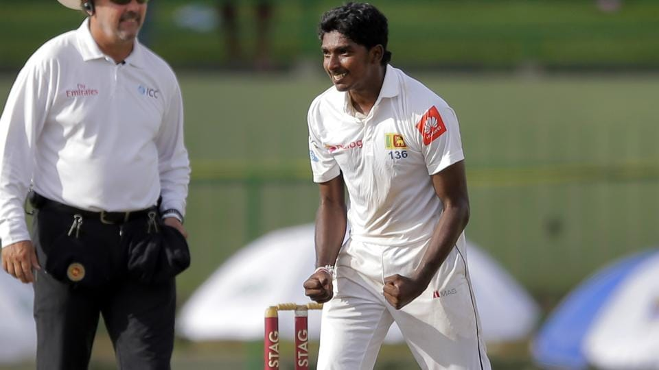 Sri Lanka's Lakshan Sandakan, right, celebrates the dismissal of India's captain Virat Kohli during the first day's play of their third Test match in Pallekele.