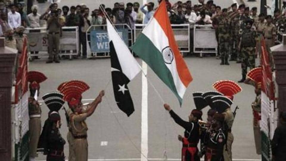 Pakistani rangers (wearing black uniforms) and Indian Border Security Force officers lower their national flags during a daily parade at the Pakistan-India joint check-post at Wagah border, near Lahore.