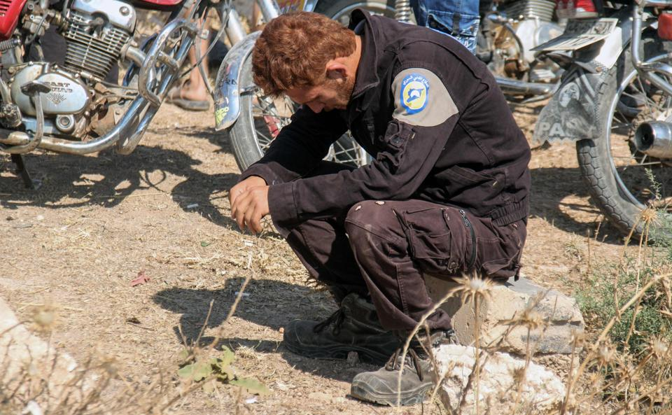 A member of the Syrian civil defence volunteers, also known as the White Helmets, mourns as colleagues bury his fellow comrades in Sarmin, a jihadist-held town 9 km east of Idlib on August 12, 2017.
