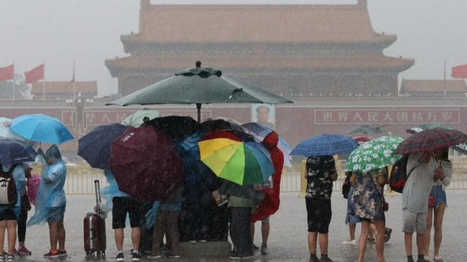 Tourists hold umbrellas as they visit Tiananmen Square during a rainstorm in Beijing on Saturday.