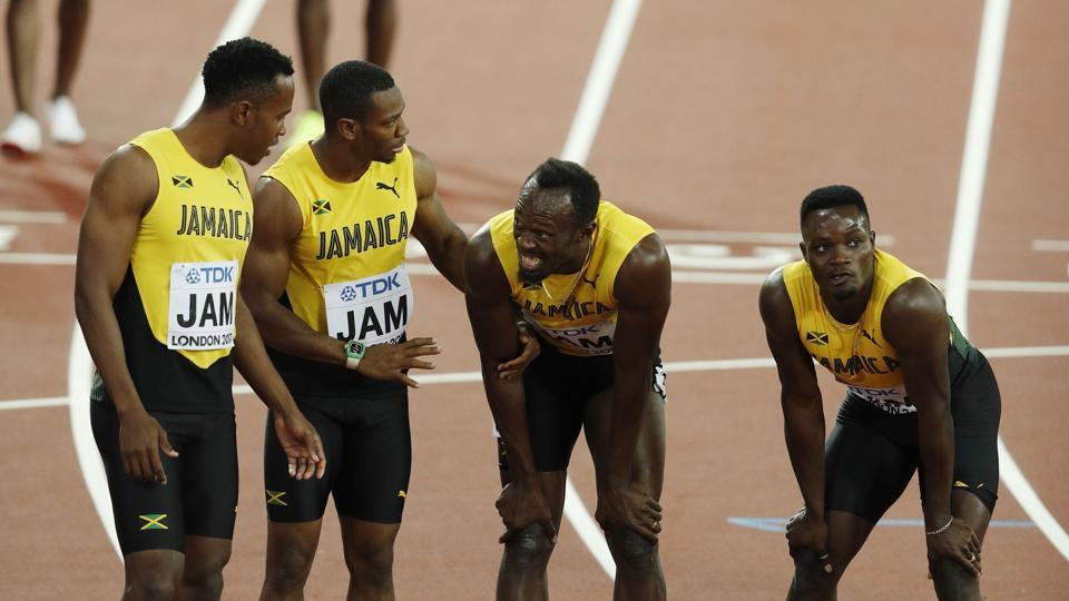 Jamaica's Julian Forte (L), Yohan Blake (2L) and Omar McLeod (R) console Jamaica's Usain Bolt (2R) after Bolt pulled up injured in the final of the men's 4x100m relay athletics event at the 2017 IAAF World Championships at the London Stadium in London on Saturday.