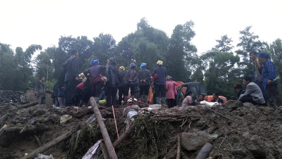 Villagers stand near debris as they wait for rescuers to work following a landslide in Gengdi village in southwestern China's Sichuan province on August 8. Continuous rainfall has blocked several road sections in Tibet.