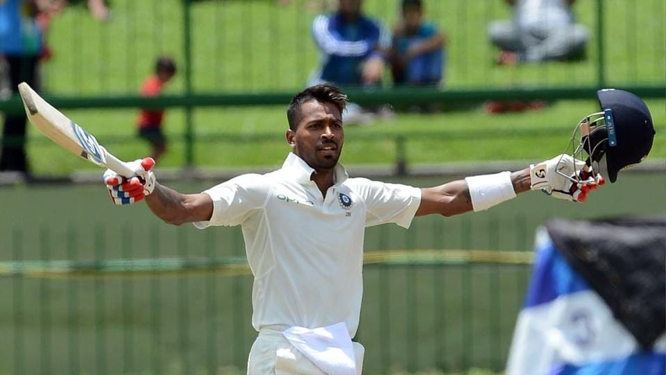 Hardik Pandya raises his bat and helmet in celebration after completing his maiden century in India's third Test against Sri Lanka at Pallekele.